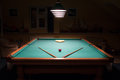 stock image of  Billiard table with balls and cues in the light of the lamps