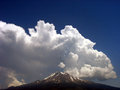 Billowing clouds over mountain peak dramatic above a snowy Royalty Free Stock Image
