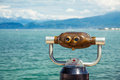 Binocular for observation telescope of boats and mountains situated on lake coast Stock Photos
