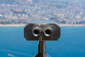 Binoculars in the background the outline of the city and the turquoise sea Royalty Free Stock Images