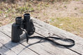 Binoculars modern with neck strap put on old wood table Royalty Free Stock Images