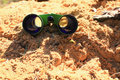 Binoculars on the sand. Royalty Free Stock Photo