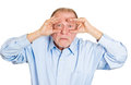 Binoculars surprised man closeup portrait of senior mature serious peeking through his fingers like searching for something Stock Photos