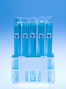 Bio hazardous substance in laboratory test tubes front view of experimental filled with transparent blue and marked as against a Stock Photos
