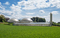 Biogas plant and sewage sludge drying greenhouse for solar in a farm behind a young green cornfield Royalty Free Stock Image