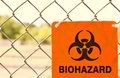 Biohazard sign attached to a chain link fence Royalty Free Stock Images