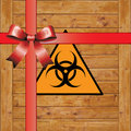 Biohazard wooden box marked with symbol for biological hazard wrapped as a gift with red ribbons and bow Royalty Free Stock Image