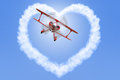 Biplane creating a heart shape in the sky red shaped cloud bright blue Royalty Free Stock Photo