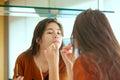 Biracial teen girl putting makeup on in mirror Royalty Free Stock Photo