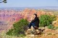 Biracial teen girl sitting along rock ledge at grand canyon arizona Stock Image