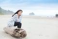 Biracial teen girl sitting on log quietly looking at ocean Royalty Free Stock Photo