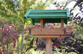 Bird feeder a birdfeeder table or tray are devices placed outdoors to supply food to birds feeding Royalty Free Stock Photography