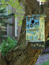 The bird hotel colorful birdhouse hangs from tree trunk vertical Royalty Free Stock Images
