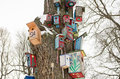 Bird house nesting box snow tree trunk winter decorative colorful painted birdhouse boxes hang on large old covered with in Royalty Free Stock Photography