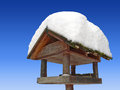 Bird house with snow cover and blue sky against Royalty Free Stock Photos