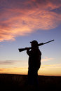 A bird hunter silhoutted against a dramatic sunset with shotgun Stock Photography