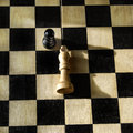 Bird view fallen white king black victorious pawn Royalty Free Stock Images