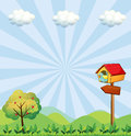 A birdhouse at the hilltop with an arrowboard illustration of Royalty Free Stock Photo