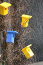 Birdhouses colored on the tree yellow and blue handmade nesting box Royalty Free Stock Image