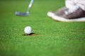 Birdie putt golf ball falling into hole after on green Stock Photo