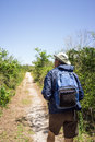 Birdwatching man hiking on a path in national park mature hat backpack and windbreaker an arid landscape Royalty Free Stock Image