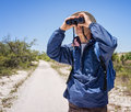 Birdwatching man hiking on a path in national park mature hat backpack and windbreaker with binoculars Stock Images