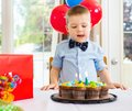 Birthday boy licking lips while looking at cake on table Stock Image