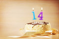 Birthday cake with burning candle as a number fourteen focus on the Stock Photo