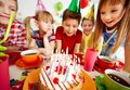 Birthday cake group of adorable kids looking at with candles Royalty Free Stock Photos