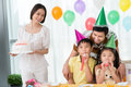 Birthday cake image of a father having fun with his children while a mother holding on the foreground Royalty Free Stock Images