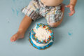 Birthday cake smash baby studio blue background a a with sprinkles Royalty Free Stock Images