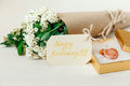 Birthday Card with Golden Present Box with Glass Heart. Bouquet White Small Flowers in Brown Craft Paper with String.White Wooden Royalty Free Stock Photo