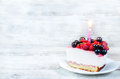 Birthday cheesecake with candle raspberries red and black curr currants on a white wood background toning selective focus on Stock Photography