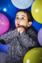 Birthday child surrounded by balloons at a party sweet fun Stock Photo