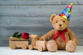 Birthday concept, teddy bear in party cap and wooden toy train Royalty Free Stock Photo