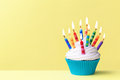 Birthday cupcake against a yellow background Stock Image