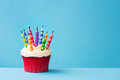 Birthday cupcake with candles blown out against a blue background Royalty Free Stock Images