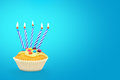 Birthday cupcake and candles with on blue background text space Stock Photos