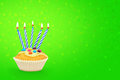 Birthday cupcake with candles and confetti on green background Stock Photo