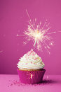 Birthday cupcake with a sparkler against pink background Royalty Free Stock Photo