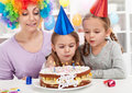 Birthday girl blowing out candles on a cake Stock Photo