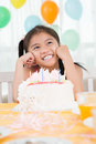Birthday girl vertical image of a cheerful sitting in front of the cake Royalty Free Stock Photos