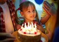 Birthday magic cute girl surrounded by her friends and cake with candles Royalty Free Stock Photos