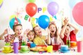 Birthday party group of adorable kids having fun at Stock Photos