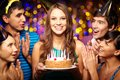 Birthday party portrait of joyful girl holding cake surrounded by friends at Royalty Free Stock Image