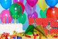 Birthday party still life with cake balloons presents streamers and hats Stock Photo