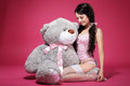 Birthday sensual girl with teddy bear sitting and smiling dearness erotic happy woman over pink Royalty Free Stock Image