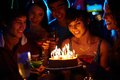 Birthday wonder portrait of joyful girl looking at cake surrounded by friends at party Stock Photos