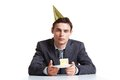 Birthday at work portrait of young businessman in cap looking camera with piece of cake in front of him Royalty Free Stock Photography