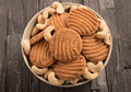 Biscuits and cashew in a bowl on black wooden background Stock Photo